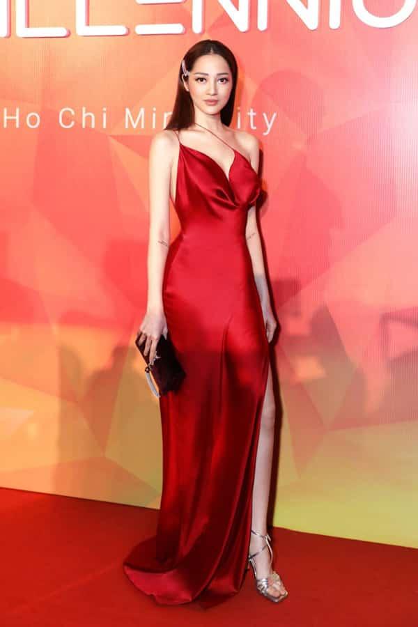 Váy lụa đỏ đậm của Trần Hùng giúp Bảo Anh khoe làn da trắng sáng. Chất liệu mềm mịn đi cùng phần biến tấu hai dây độc đáo càng khiến người mặc cuốn hút hơn.