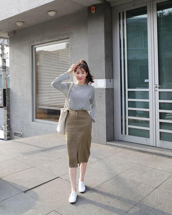 Phong cách năng động nhưng không kém phần nữ tính cho nàng văn phòng với áo kẻ sọc thủy thủ, chân váy vải thô, túi tote và giầy đế bệt.