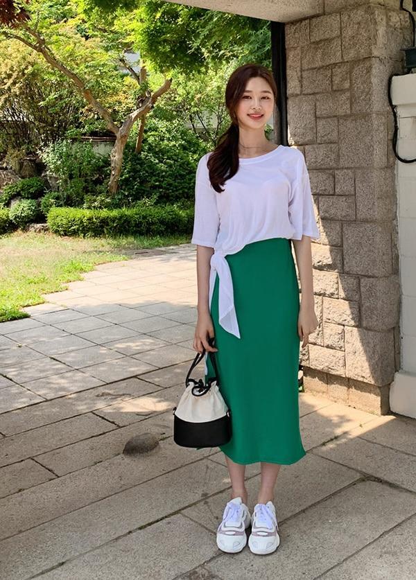 Bộ đồ gồm áo phông thắt nơ ở eo và chân váy dài, giày thể thao và túi bucket phù hợp những cô gái thích phá cách.