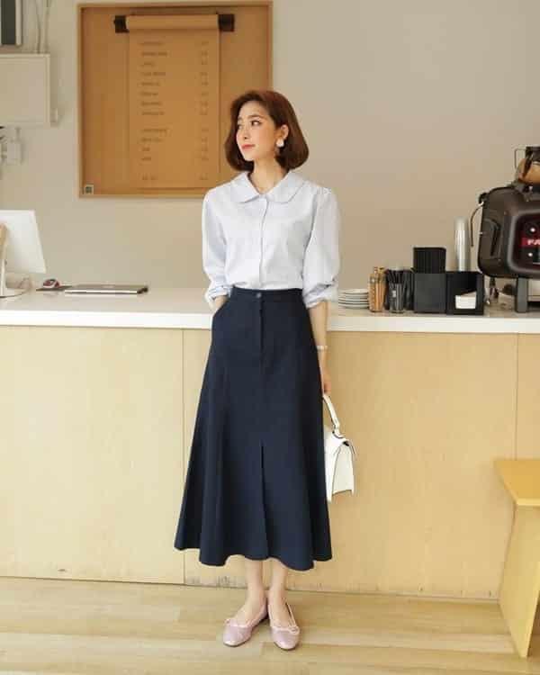 Kiểu váy này cũng phù hợp với sơ mi cổ lá sen. Bạn có thể chọn cả bộ đơn sắc theo phong cách tối giản đi cùng túi xách và giày màu pastel.