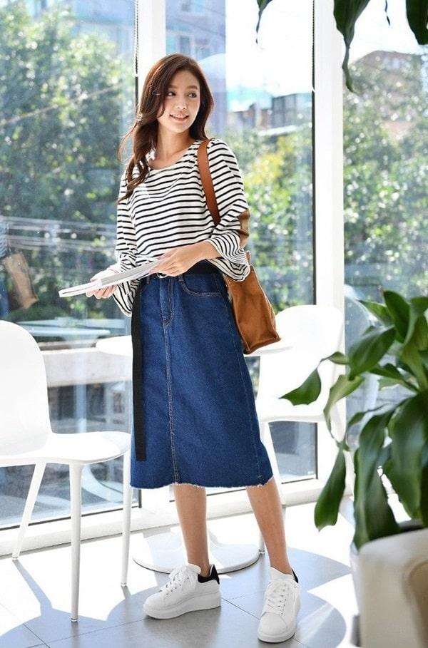 Nếu muốn tạo nên sự năng động, có thể chọn chân váy chất liệu denim, sneakers và áo phông kẻ ngang.
