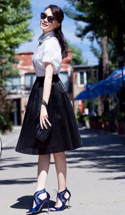 Một chiếc váy xếp ly xòe với phom cứng chất vải nặng mặc cùng áo sơ mi trắng sẽ khiến giáo viên trẻ hơn
