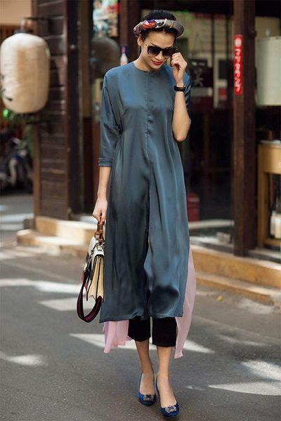 Chiếc áo dài cách tân không có họa tiết được khéo léo tạo điểm nhấn bằng những vạt màu hồng hai bên, phối cùng chiếc quần ống túm màu đen tạo sự tinh tế.