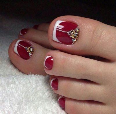 Móng chân màu đỏ đính thêm đá và họa tiết tạo nét nữ tính, sang trọng