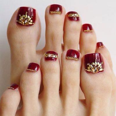 Móng chân sơn đỏ đính đá mang đến sự sang trọng, quý phái
