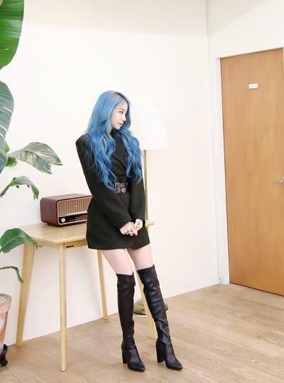 Cô nàng mang boot cao trên gối đồng hiệu với thắt lưng và chiếc blazer dáng dài