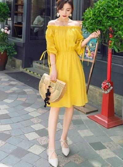 Đầm trễ vai màu vàng tươi cực kỳ phù hợp với không khí mùa hè. Với phần tay phồng, thiết kế này trông rất cổ điển