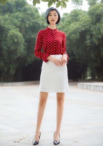 Áo sơ mi đỏ chấm bi kết hợp với chân váy chữ A màu trắng giúp các quý cô có vẻ ngoài thật nổi bật
