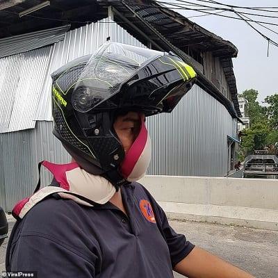 Một người đàn ông sử dụng áo ngực làm khẩu trang khi đi đường.