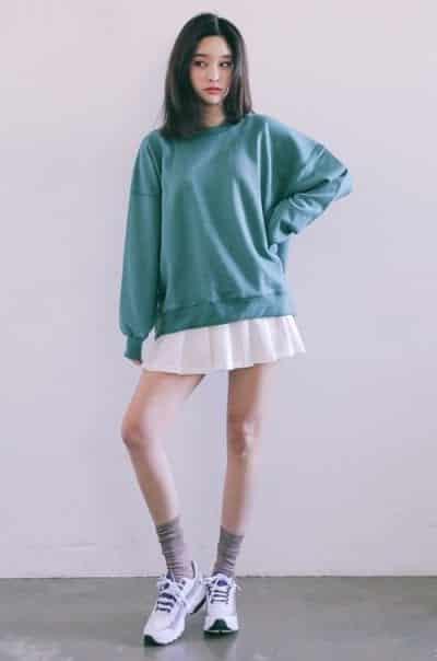 Áo thun hoodie dài tay màu xanh pastel kết hợp hài hòa với váy xòe xếp ly màu trắng, phối hợp thêm một đôi tất cổ trung và giày sneaker
