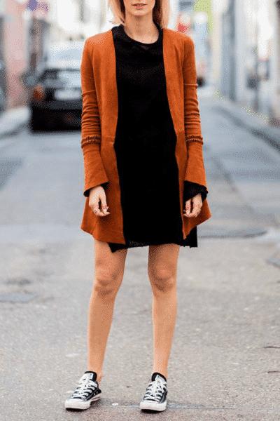 Đôi giày Converse đen cơ bản phối với váy mini và áo khoác dạ retro
