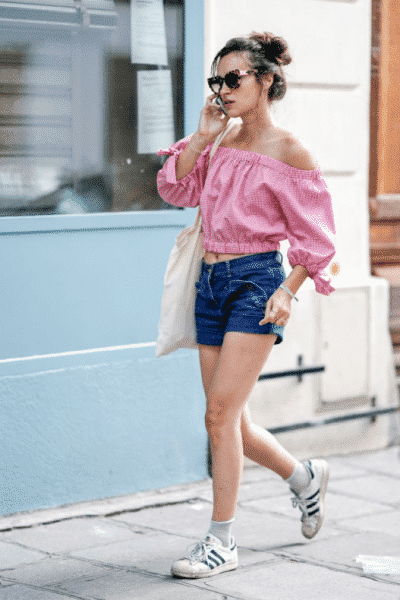 Áo trễ vai kẻ gingham hồng trắng kết hợp với quần sooc jean nổi bật và thời trang