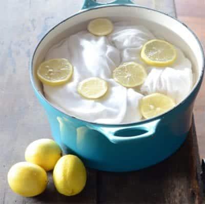 Ngâm quần áo bị phai màu trong dung dịch nước sạch và chanh để tẩy trắng
