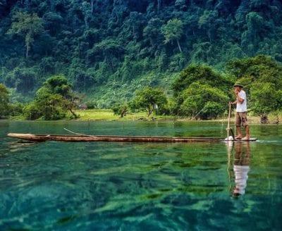 Mặt hồ trong như gương in bóng rừng cây nguyên sinh và đồi núi.