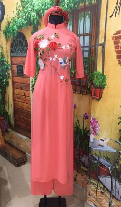 Áo dài cam thêu ruyban hình hoa – giá sỉ 225,000đ /cái.